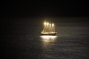 barca a vela nel mare di notte foto