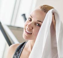 ragazza graziosa del ritratto con l'asciugamano dopo l'allenamento foto
