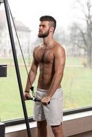 atleta maschio che fa esercizio pesante per il tricipite foto