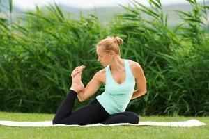 donna che fa yoga posa con una gamba sola del piccione re foto