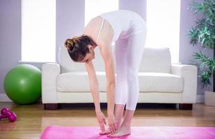 donna adatta che fa yoga sulla stuoia foto