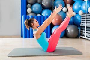Pilates teaser esercizio donna sulla stuoia palestra coperta foto