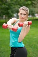 ragazza sportiva esercizio con manubri nel parco foto