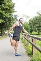 uomo forte atletico facendo si estende prima di esercitare, all'aperto. foto