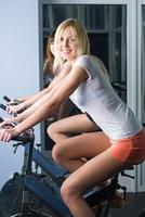 ragazze attraenti su simulatori di biciclette foto