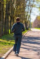 uomo che corre nel parco vista da dietro foto