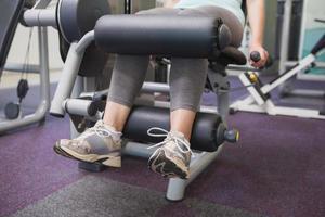 donna adatta utilizzando macchina pesi per le gambe foto