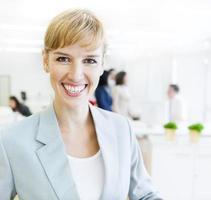donna caucasica di affari che sorride alla macchina fotografica foto