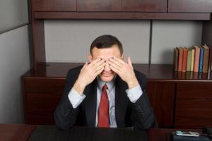 non vedere alcun male - uomo d'affari caucasico che copre la scrivania degli occhi foto