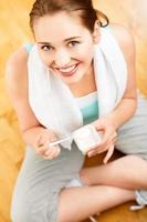 alto ritratto chiave giovane donna caucasica che mangia yogurt a casa foto