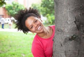 donna caraibica dietro un albero