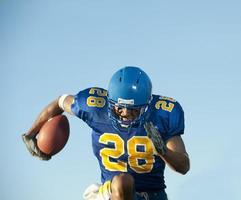 giocatore di football americano che tiene un pallone da calcio mentre corre foto