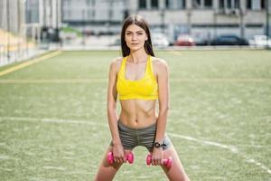 allenamento muscolare con manubri. la donna giovane e magra si allena con