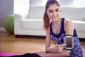 donna adatta che utilizza smartphone nella fascia da braccio foto