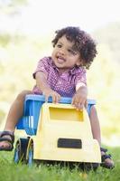 ragazzo che gioca sull'autocarro con cassone ribaltabile del giocattolo all'aperto foto