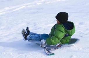 ragazzo che sledding giù la collina nevosa foto