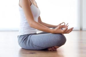 bella giovane donna facendo esercizi di yoga a casa. foto