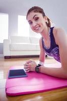 donna adatta che fa tavola sul tappetino foto
