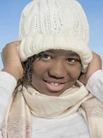 ragazza che gioca con un berretto di lana bianca sotto il sole foto