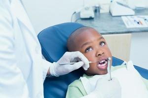 ragazzo che ha i denti esaminati dal dentista foto
