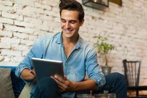 uomo casuale che per mezzo del sorriso del computer della compressa foto