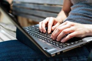 mani femminili che lavorano al primo piano del computer portatile all'aperto foto