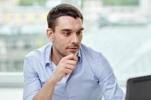 giovane imprenditore con computer portatile in ufficio foto