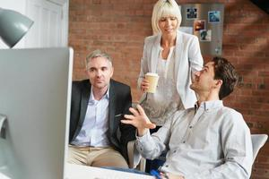 colleghi che lavorano al computer in ufficio occupato foto