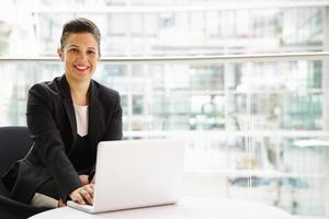 donna di affari che per mezzo del computer portatile che guarda alla macchina fotografica foto