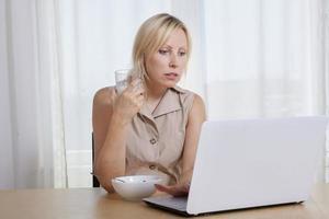 donna facendo colazione davanti al computer foto