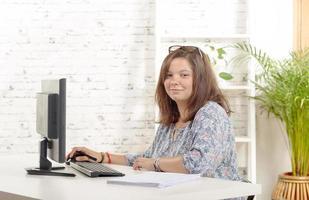 Ritratto di una ragazza adolescente al suo computer foto