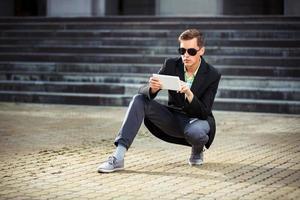 giovane che per mezzo di un computer tablet all'aperto foto