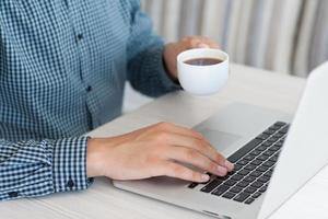 uomo che lavora a un computer portatile e bere caffè foto