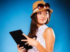 ragazza che per mezzo del lettore del libro elettronico del computer della compressa. foto