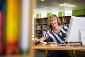 studente che studia in biblioteca con il computer foto