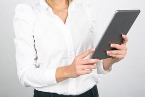 donna di affari che per mezzo del computer della compressa su fondo bianco foto