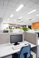 computer e sedia in un cubicolo in un posto di lavoro in ufficio foto