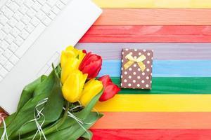 computer bianco e bouquet di tulipani con regalo foto