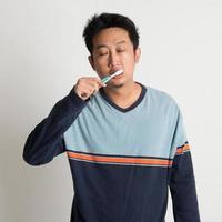 maschio asiatico lavarsi i denti foto