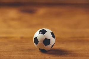 pallone da calcio in plastica in miniatura sul tavolo di legno foto