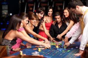 gente sorridente e commerciante che giocano alla roulette foto