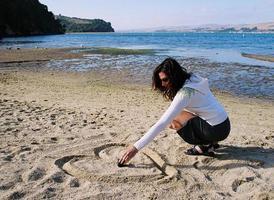la donna raggiunge per la scatola dell'anello della sabbia della spiaggia foto