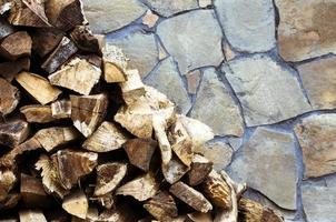 legna da ardere su sfondo muro di pietra foto