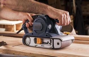 falegname lavora con levigatrice a nastro in carpenteria
