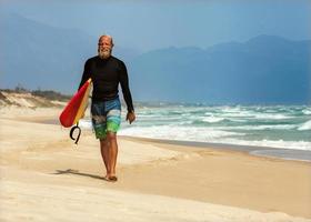surfista al mare è in piedi con una tavola da surf foto