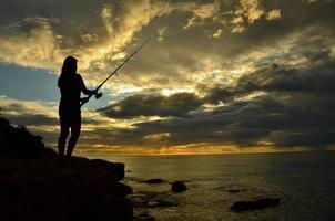 pesca stando in piedi su una scogliera in hawaii foto