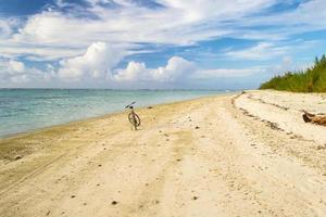 spingere la bicicletta solitaria su una spiaggia deserta tropicale