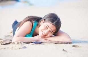 ragazza teenager biraziale che si trova sulla spiaggia sabbiosa, che riposa e che sorride foto