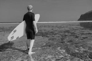surfista con tavola da surf su una costa