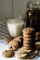 biscotti al cioccolato su blocco di legno con un bicchiere di latte foto